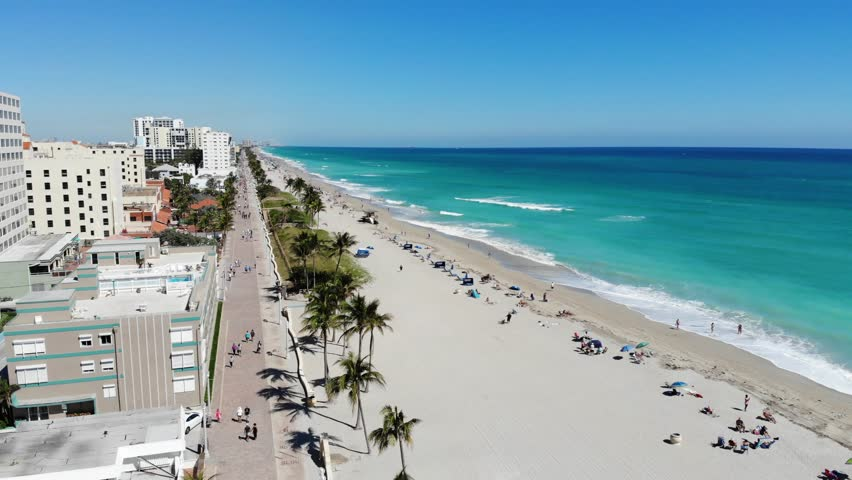 Aerial view of Hollywood Beach, Florida, near Miami Beach. The view encompasses the luxury hotel chains along the waterfront. The boardwalk and people enjoying the beach are visible.