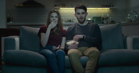 Couple watching television together at night, sharing popcorn.