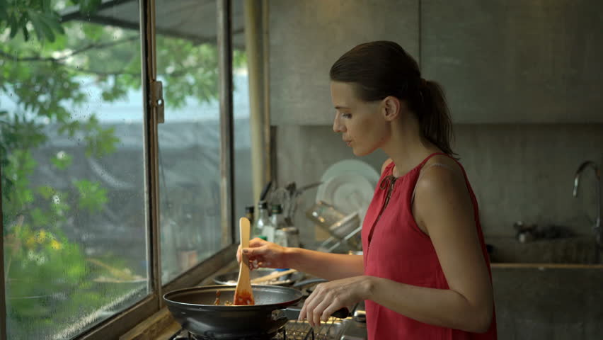 Young woman cooking and tasting meal in kitchen at home  | Shutterstock HD Video #1008867929