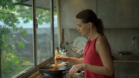Young woman cooking and tasting meal in kitchen at home