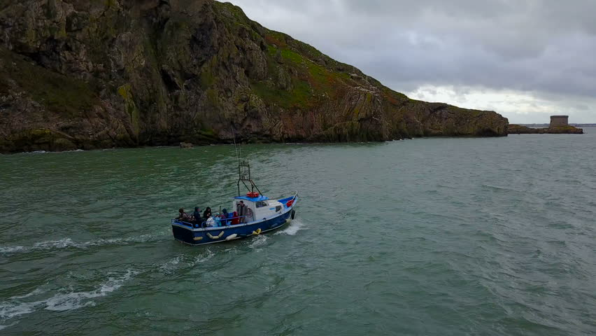 Aerial view of boat with unre?ognizible people in sea sailing near the Ireland`s Eye island, Howth, Ireland   Shutterstock HD Video #1008874799