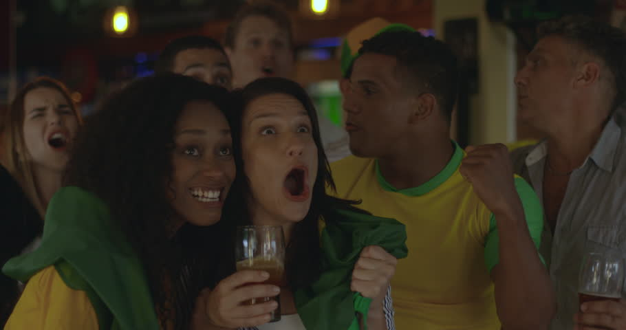 Brazilian football fans celebrating victory while watching match in sports bar, slow motion