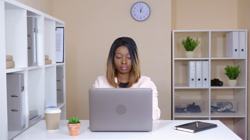 Beautiful woman works in room with casual modern interior. attractive businesswoman using laptop sitting at the white desk. entrepreneur looking at the camera with cheerful friendly smile | Shutterstock HD Video #1008896309