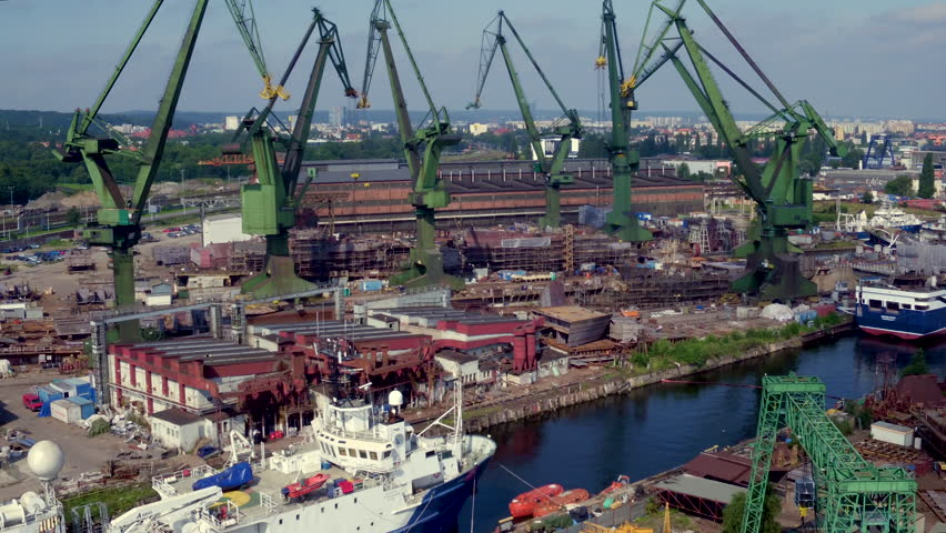 Drone daytime footage of industrial part of Gdansk. View over the Gdanska Shipyard, cranes, postindustrial climat of old machinery in a scenery of Martwa Wisla river.