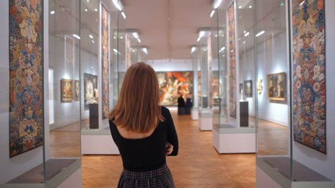 WARSAW, POLAND - MARCH 28, 2017: National Museum in Warsaw. A slender Young woman in a Dress Is Walking Between Exhibits and Artworks in a Museum or Art Gallery
