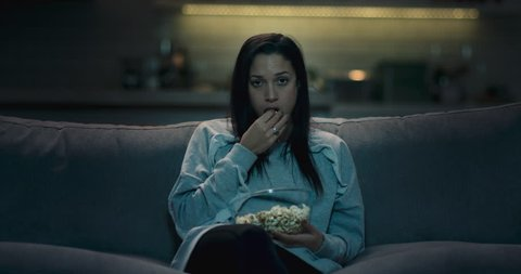 Sad, bored and depressed woman sitting on a sofa at home watching a bad movie eating popcorn