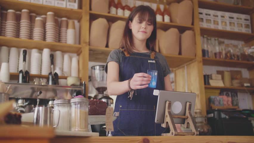 Female Deli Shop Cashier Swiping Card On Digital Tablet Reader | Shutterstock HD Video #1008922709