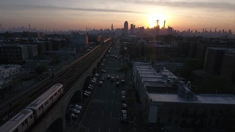 Aerial wide shot of the traffic and train going through railway in Queens at the sundown