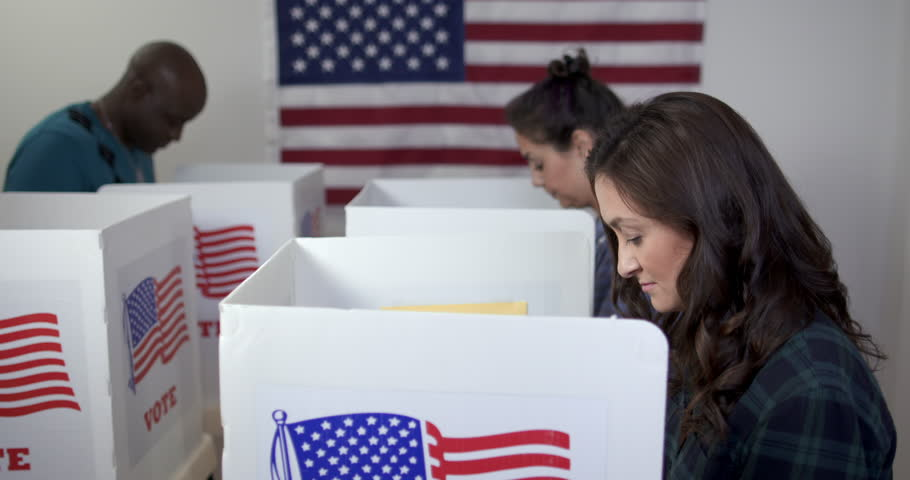 Side view MS of three people, two women and one man, Caucasian, Hispanic and African American, voting in booths at polling station. Large US flag on wall behind. Fluid head tripod, real time 4K