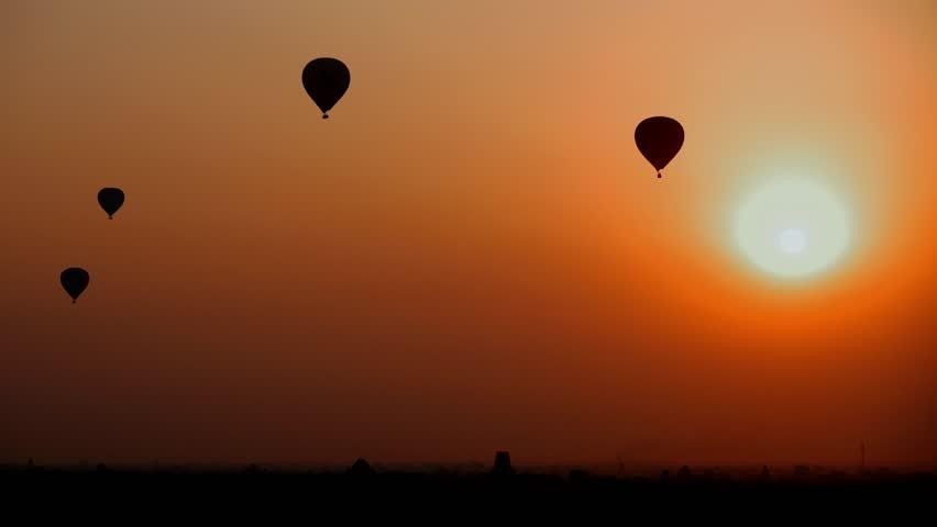 Balloons at dawn. Silhouette of balloons on an orange background. Amazing Sunset in Myanmar. Sunsrise in Burma. Orange sky. Balloons fly through the sun. Bagan. Old Bagan. Kapadokya. 4k Turkey