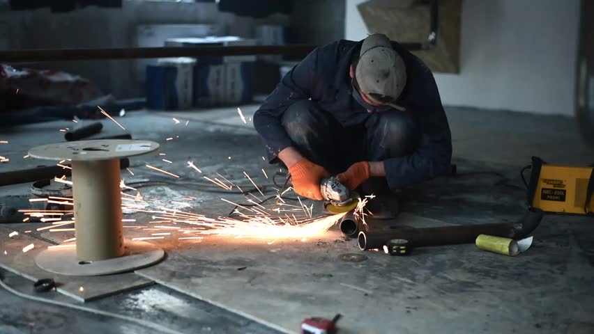 Welder at work in factory. Sparks during cutting of metal angle grinder
