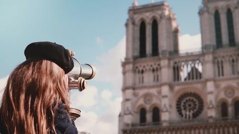 Girl child in beret looks through coin binoculars. Slow motion. Notre-Dame de Paris. Coin-operated telescope. Tourism.