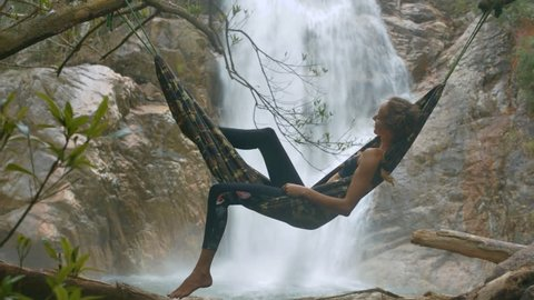 fantastic picture girl in black top soars in air on hammock against magnificent foamy waterfall streaming among rocks