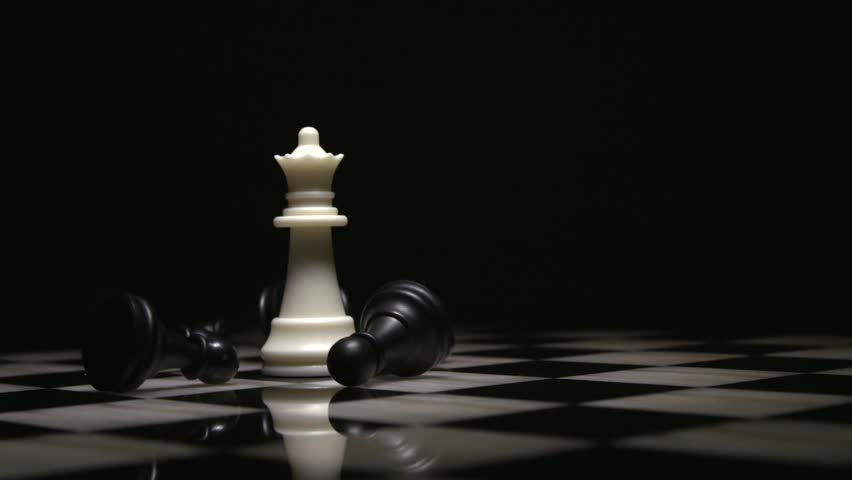 Chess queen piece surrounded by fallen black pawns