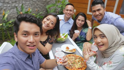 Group of friends enjoying meal at outdoor party in backyard taking selfie together