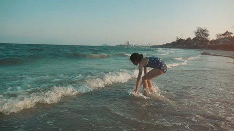Asian boy walking in waves in sunny day, slow motion