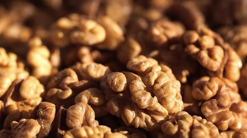 Walnut close up. product rich in minerals and vitamins. Walnut turns in a shot. Walnut kernels rotating. walnut close up lies under beams of the sun. Macro