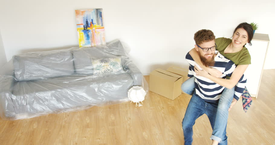 Young woman sitting on the back of her boyfriend and he spinning her around in the living room while they moving in their new home. Indoor