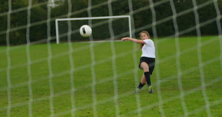 4K Young female soccer player kicking ball into goal, seen from back of the net. Slow motion. #1009004519