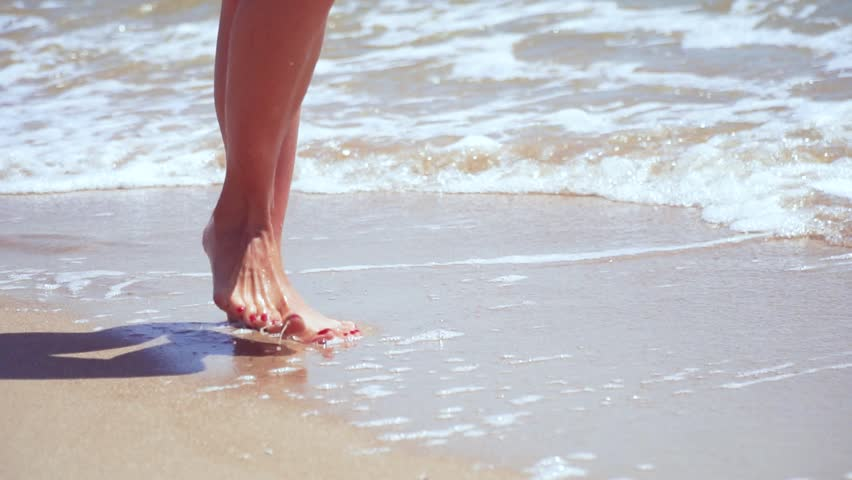 Woman's legs on the sand beach and sea water. | Shutterstock HD Video #1009009079