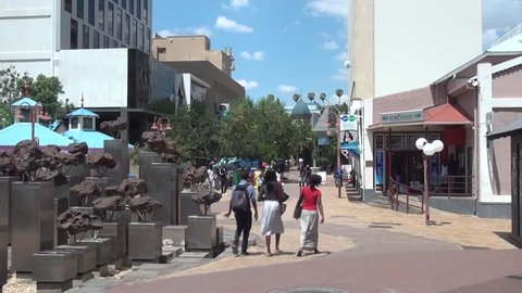 04.11.17: HD high quality summer day video footage of Post Street Mall Gibeon Meteorites monument, pedestrians walking in shopping street in city center of Windhoek, Namibia'a capital, southern Africa