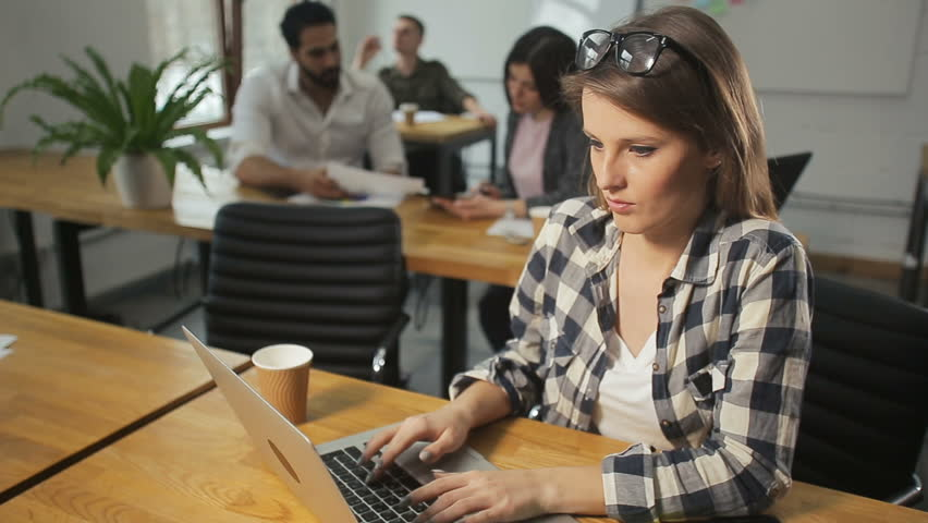 Busy long-haired woman typing on the computer, wearing checked grey and white shirt, doing the job with pleasure | Shutterstock HD Video #1009036019