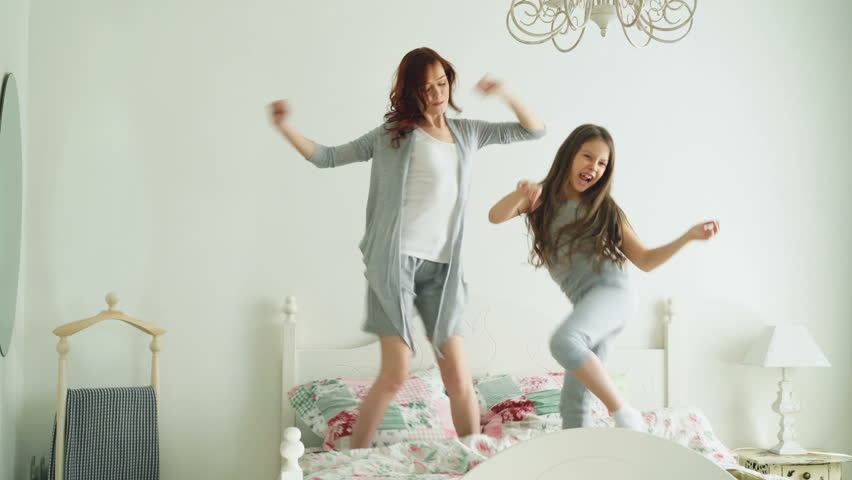 Happy family of cute daughter and young mother jumping and dancing on bed while have fun during morning on holidays at home | Shutterstock HD Video #1009046369