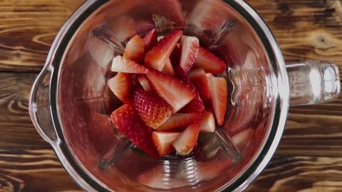 Pouring milk in blender with strawberry, super slow motion video