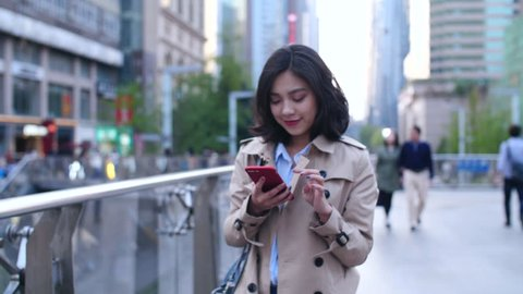 slow motion  of pretty happy young asian woman walking in the city street while using smart phone at afternoon