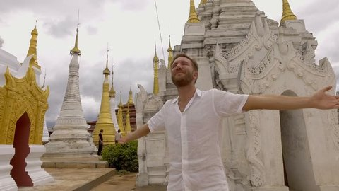 Young man contemplating temples in Myanmar arms outstretched, feeling the freedom of travel. People travel Asia concept