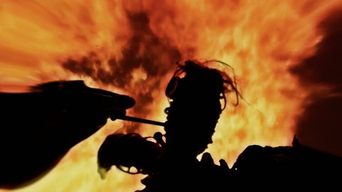 Lens distorted scene: the scay silhouette of a cursed voodoo doll, pierced by big rusty nails, over a fiery fire.