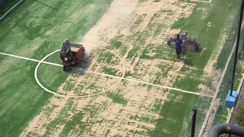 Workers are improving futsal field or small football field by sanding on artificial grass