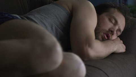 Drunk man sleeping on living room sofa in underwear, lazy bachelor lifestyle