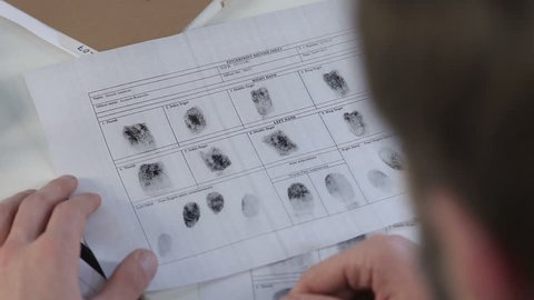 Police officer checking fingerprints file with magnifying glass, identification