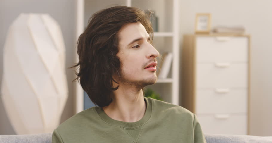 Close up of the young attractive man with a long hair looking at the side then turning his head to the camera and smiling in the nice room. Portrait. Indoors | Shutterstock HD Video #1009174019