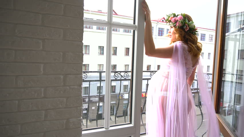 Pregnant woman in pink peignoir on a balcony