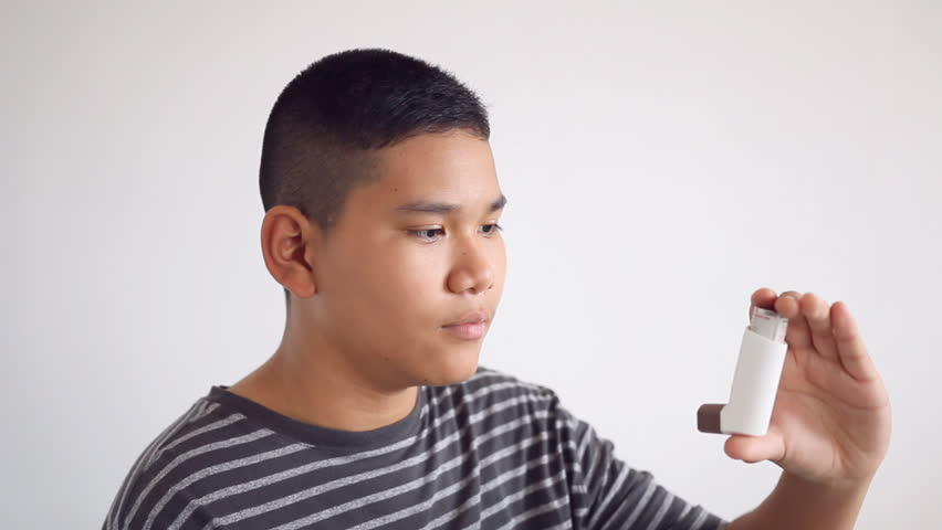 Asthma - Asian teenage boy using an inhaler for asthma and respiratory diseases. Inhalation treatment of respiratory diseases. Allergy and bronchial asthma concept.