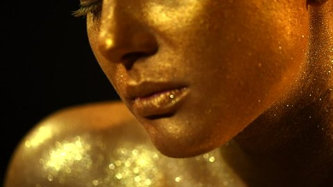 High Fashion model woman in golden bright sparkles posing in studio, portrait of beautiful sexy girl, trendy glowing gold skin make-up. Art design make up. Glitter metallic shine makeup 4K slow motion