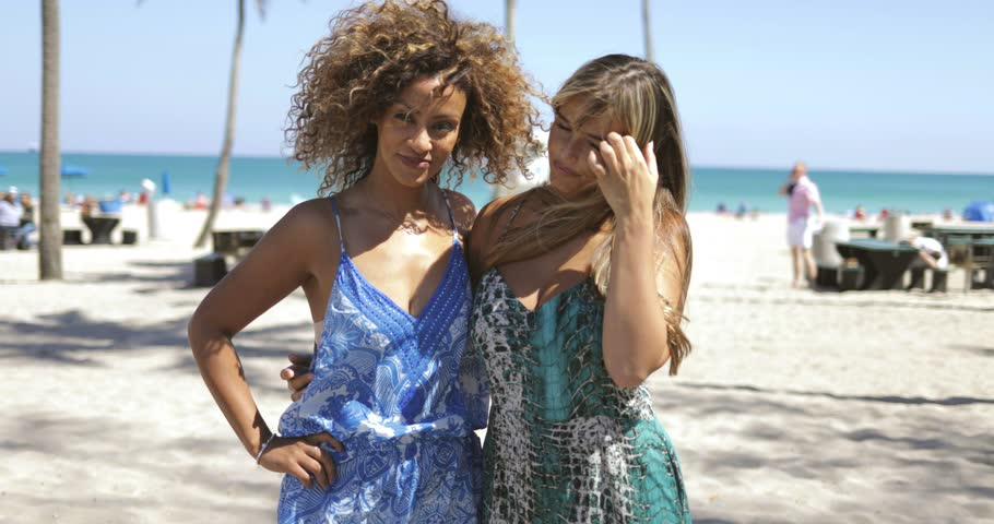 Beautiful black woman with friend in trendy summer outfits standing together on beach of ocean and looking at camera.