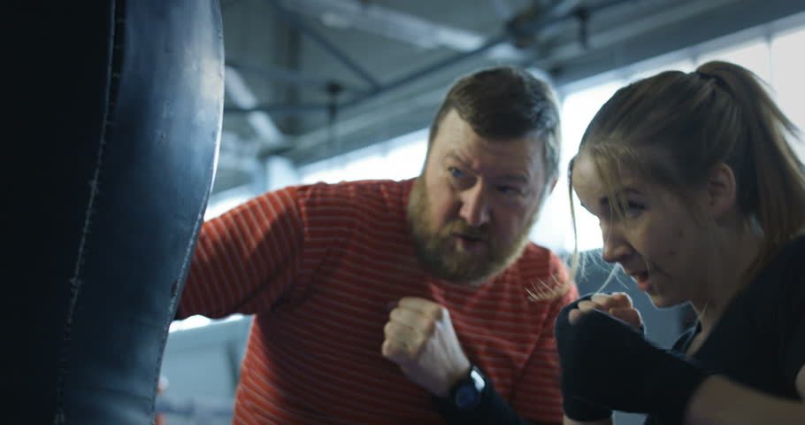 Bearded boxing trainer prepares a young woman for competitions.
