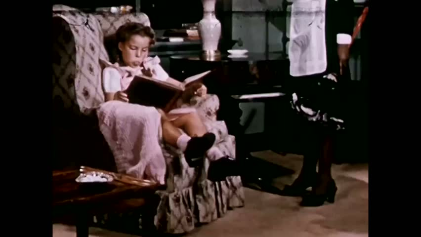 CIRCA 1940s - A little girl reads and blows a bubble with her gum while a maid brings her a new light bulb. | Shutterstock HD Video #1009213259