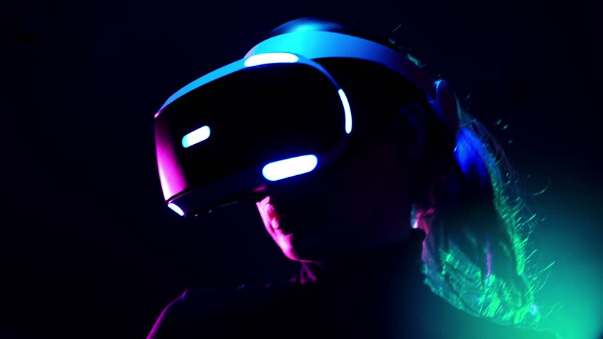 Young woman in VR headset using gamepad have fun and play interactive video game. Virtual reality helmet on black background