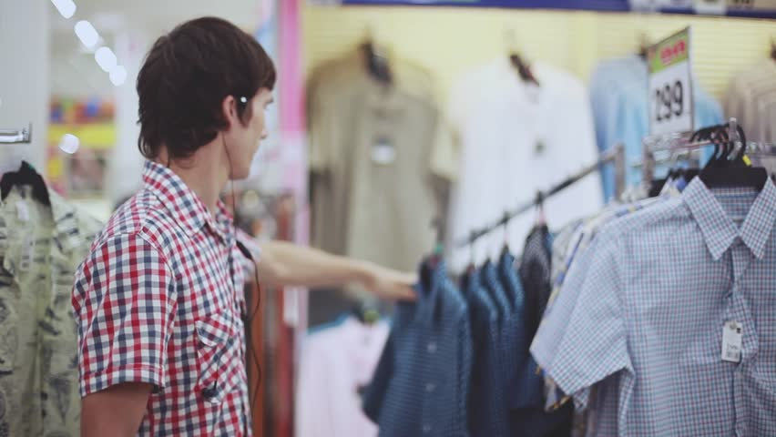 Young handsome man looking at shop and listens to music with headphones. Shopping on the mall for men's clothes. 1920x1080 | Shutterstock HD Video #1009226819