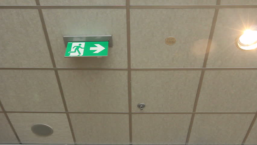 Green emergency, fire exit sign. Standard international symbol safe exit sign is hanging from the ceiling. EXIT Emergency green international exit sign is in a public building.