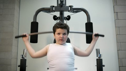thick angry kid boy trains in gym fat burning.will power children concept overweight tenacity purpose