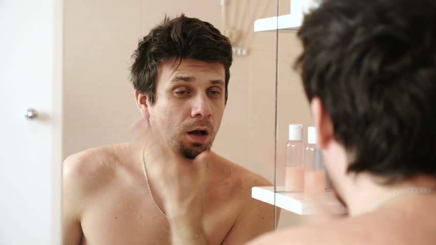 Tired man who has just woken up looking at his reflection in the mirror and slaps himself on the cheeks to wake up