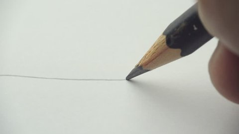 Artists hands drawing wooden pencil writes line on paper - closeup