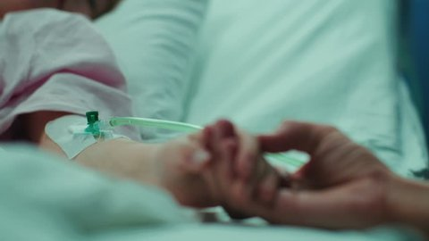 Recovering Little Child Lying in the Hospital Bed Sleeping, Mother Holds Her Hand Comforting. Focus on the Hands. Emotional Family Moment.