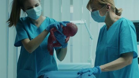 In the Hospital Woman in Labor Pushes and Gives Birth, Baby Comes out, Obstetricians Assist Delivery, Husband Supports His Wife. Side View Footage. Shot on RED EPIC-W 8K Helium Cinema Camera.