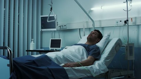Terminally Ill Male Patient Lies on a Bad In the Hospital. Melancholy and Exhausted Patient in the Palliative Care Ward. Shot on RED EPIC-W 8K Helium Cinema Camera.